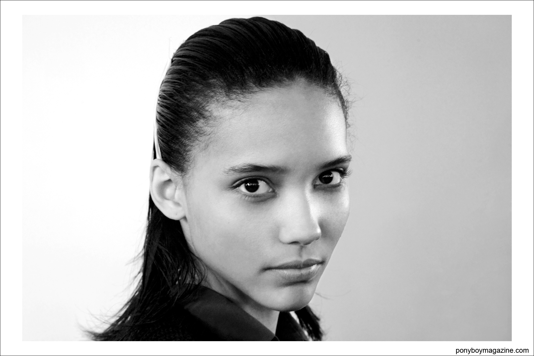 A b&w portrait of a model while getting hair and makeup done at the Jeremy Scott A/W fashion show