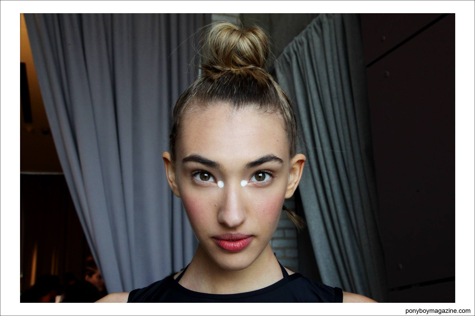 A model in a topknot hairdo, photographed backstage at The Standard in New York, at the Chromat S/S15 collection. Photo by Alexander Thompson for Ponyboy Magazine.
