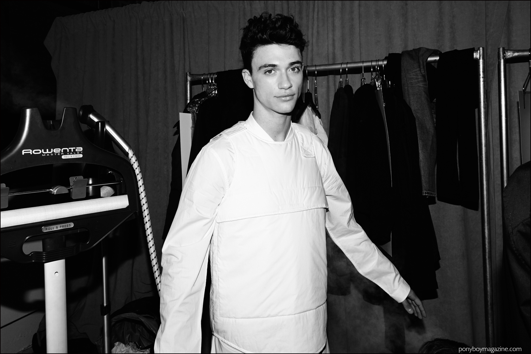 A male model photographed backstage in a white vest and shirt by Stampd F/W16 menswear label. Photography by Alexander Thompson for Ponyboy magazine NY.