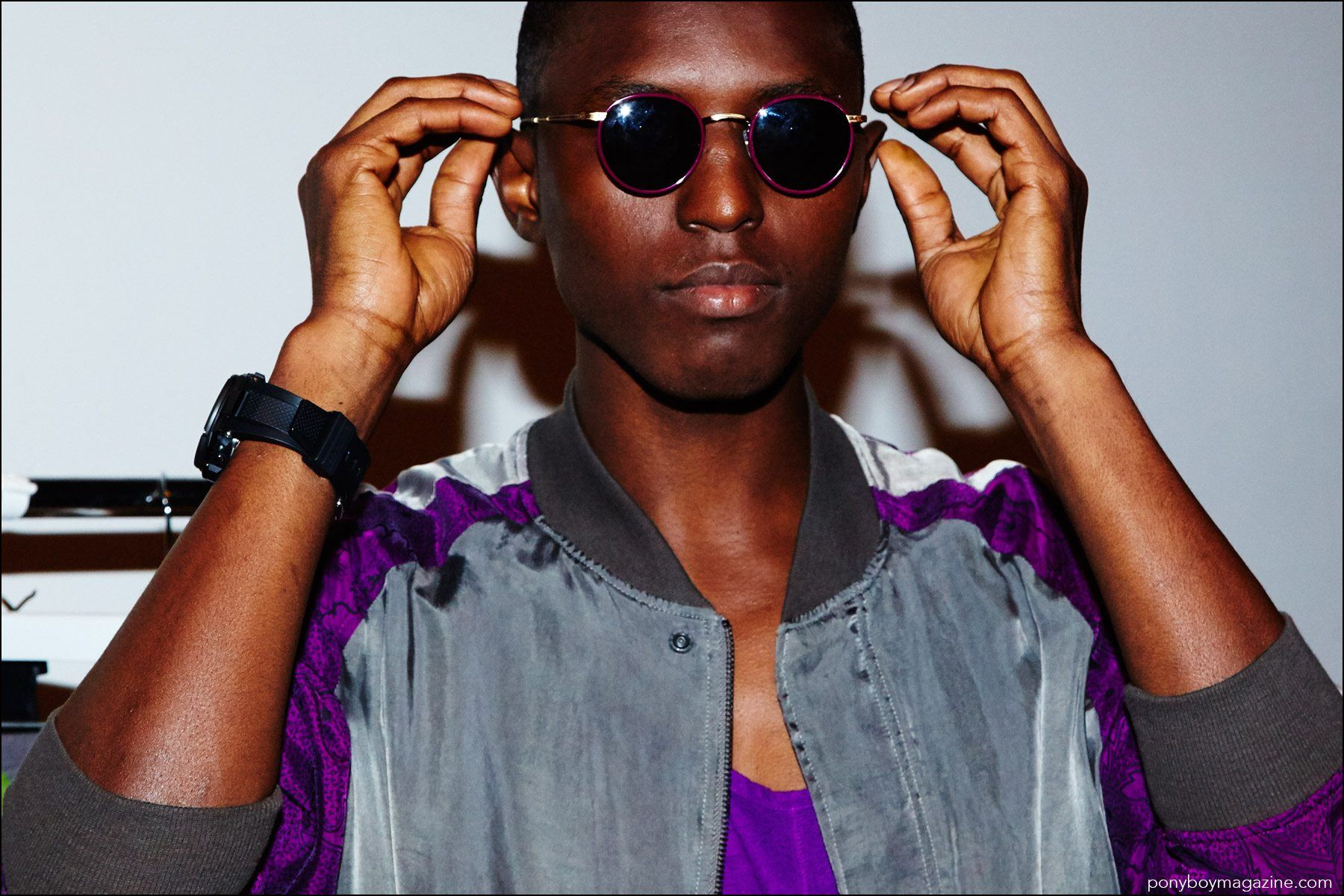A male model adjusts his sunglasses, backstage at Robert Geller Spring/Summer 2017 menswear show. Photography by Alexander Thompson for Ponyboy magazine NY.