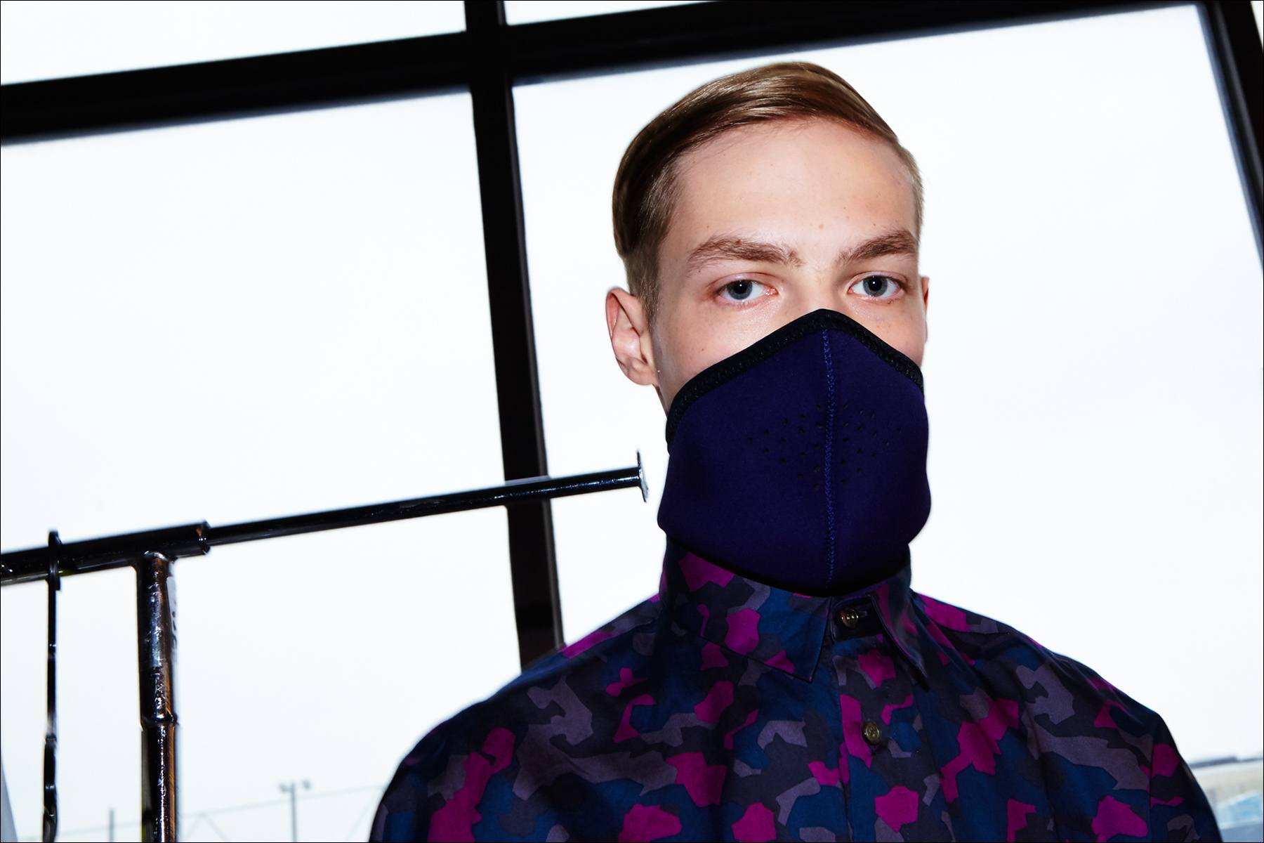 A male model photographed in a face mask and camo shirt, backstage at Robert Geller A/W17 menswear show. Photography by Alexander Thompson for Ponyboy magazine New York.
