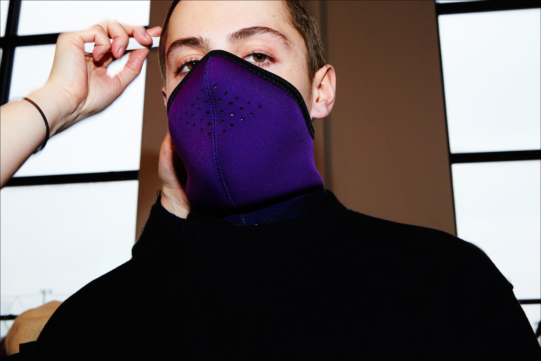 A model photographed in a purple face mask, backstage at Robert Geller A/W17 menswear show. Photography by Alexander Thompson for Ponyboy magazine New York.