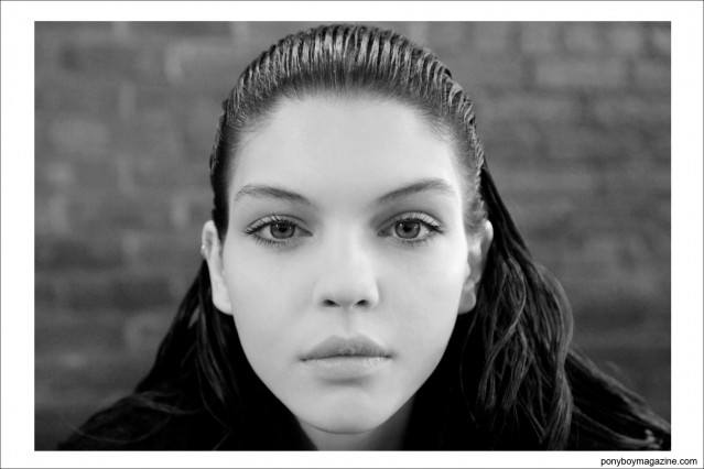 B&W photo of a brunette model, backstage at the Jeremy Scott Autumn/Winter 2014 fashion show in New York City at Milk Studios. Photographed by Alexander Thompson for Ponyboy Magazine.