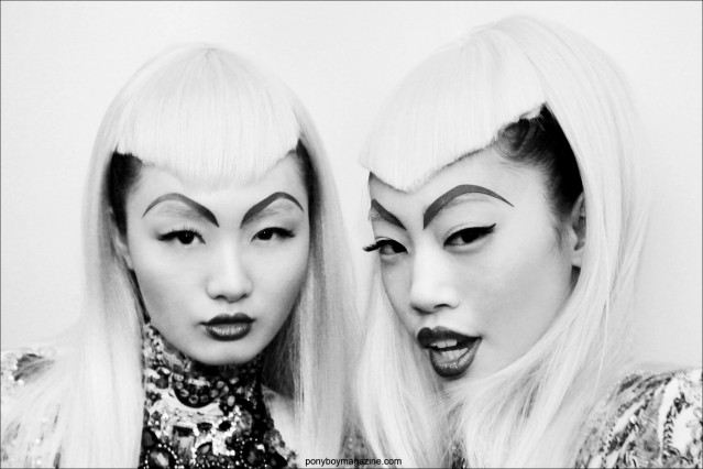 B&W photograph of two Asian models backstage at The Blonds A/W 2014 fashion show at Milk Studios. Photograph for Ponyboy Magazine by Alexander Thompson.