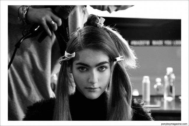 A young model gets her hair blown out backstage at the Timo Weiland A/W 2014 runway collection, photographed for Ponyboy Magazine by Alexander Thompson in New York City.