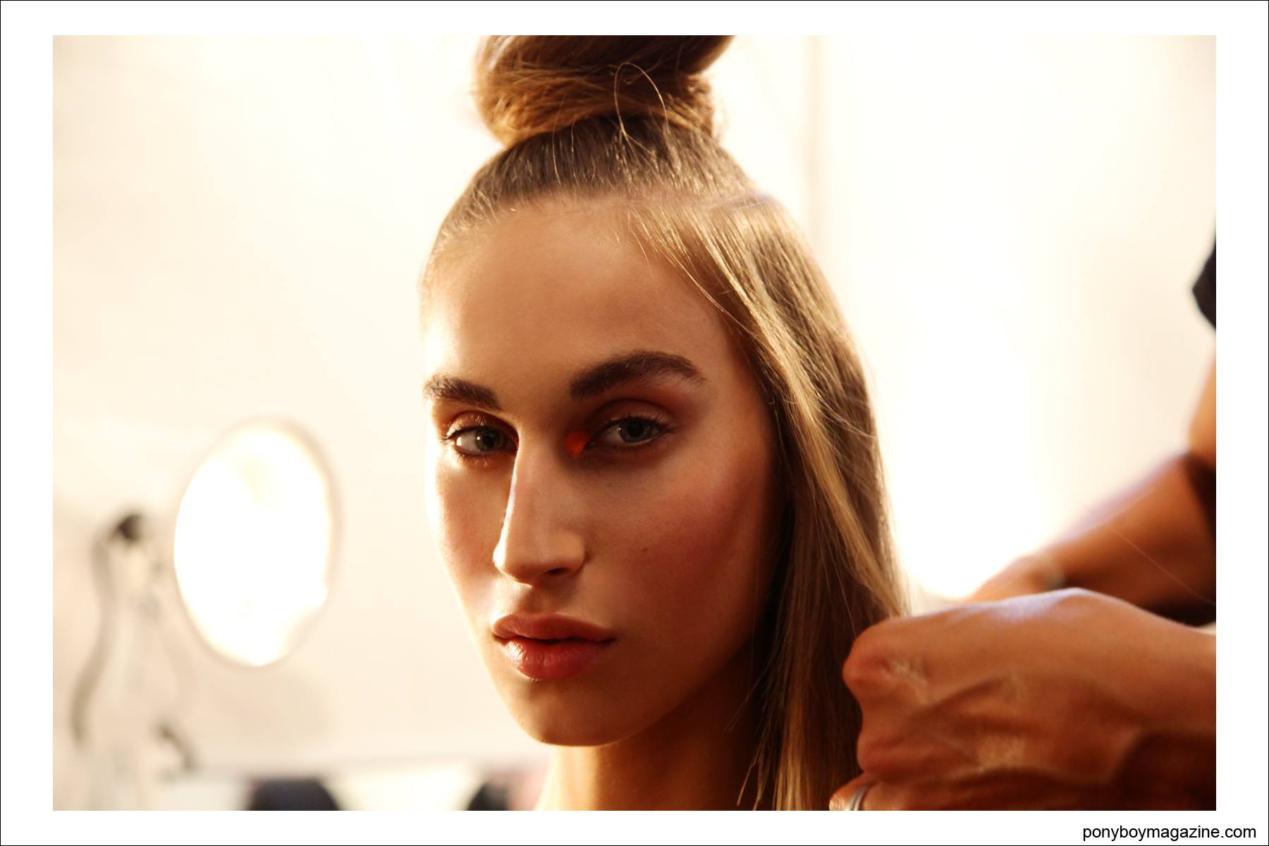 A model backstage getting her hair prepped for the Spring/Summer 2015 collection. Photograph by Alexander Thompson for Ponyboy Magazine.