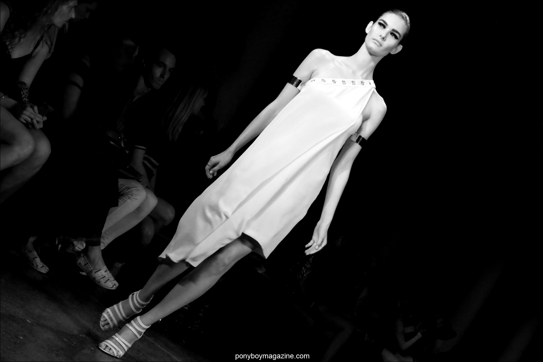 A model on the runway in a white one-shouldered dress, photographed at Milk Studios NY by Alexander Thompson for Ponyboy Magazine.