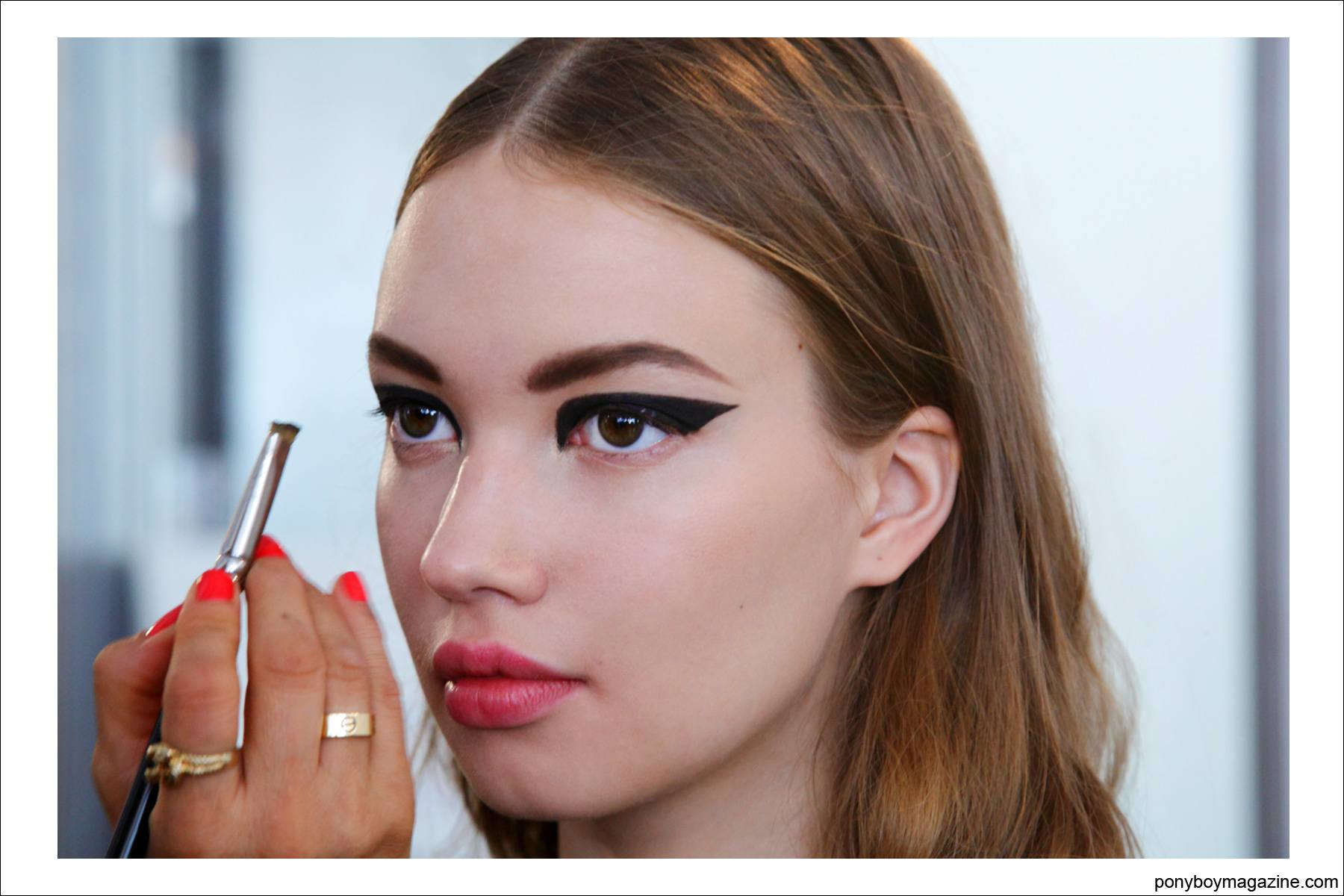 A model backstage at Cushnie et Ochs S/S15 getting her eye makeup applied. Photo by Alexander Thompson at Milk Studios, for Ponyboy Magazine.