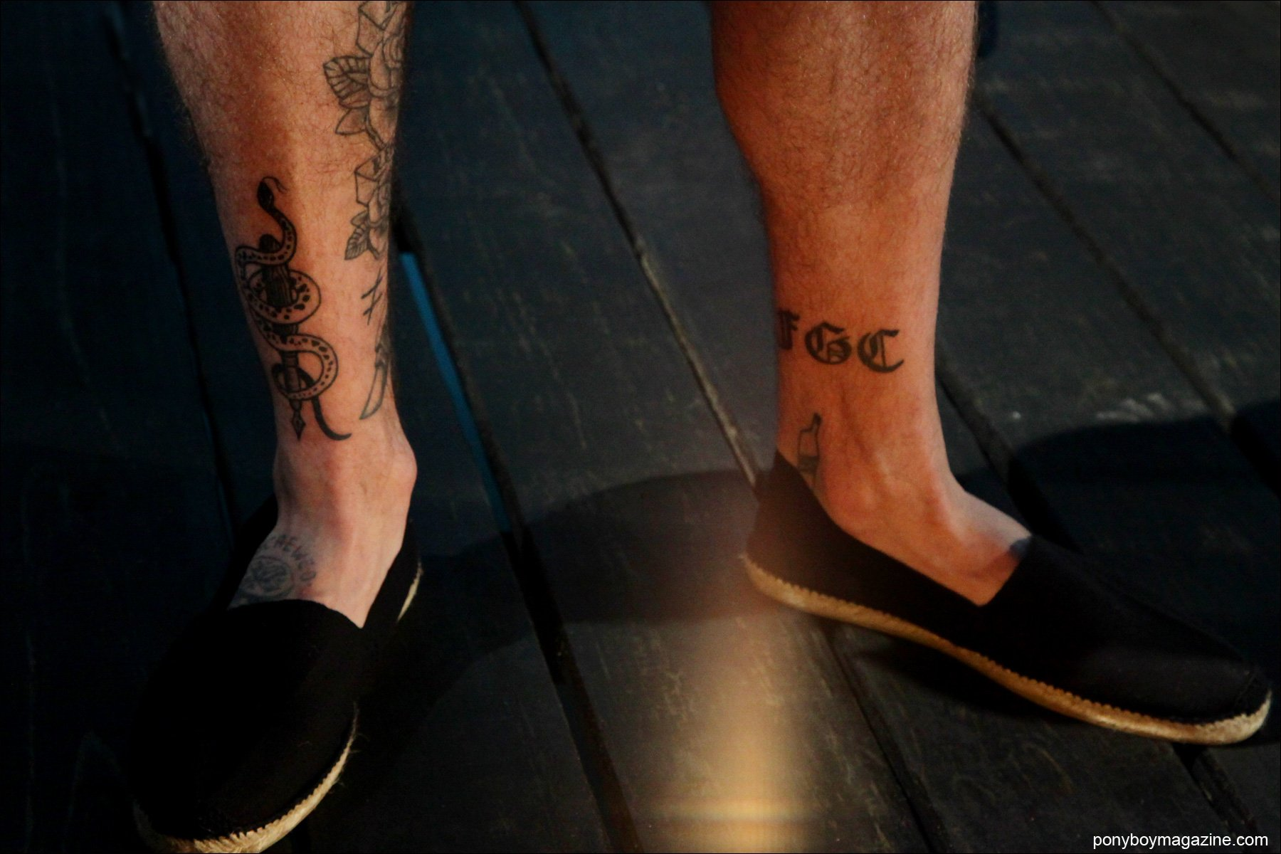 A male models tattooed legs in espadrilles, at the Rochambeau S/S15 presentation at Milk Studios NY. Photo by Alexander Thompson for Ponyboy Magazine.