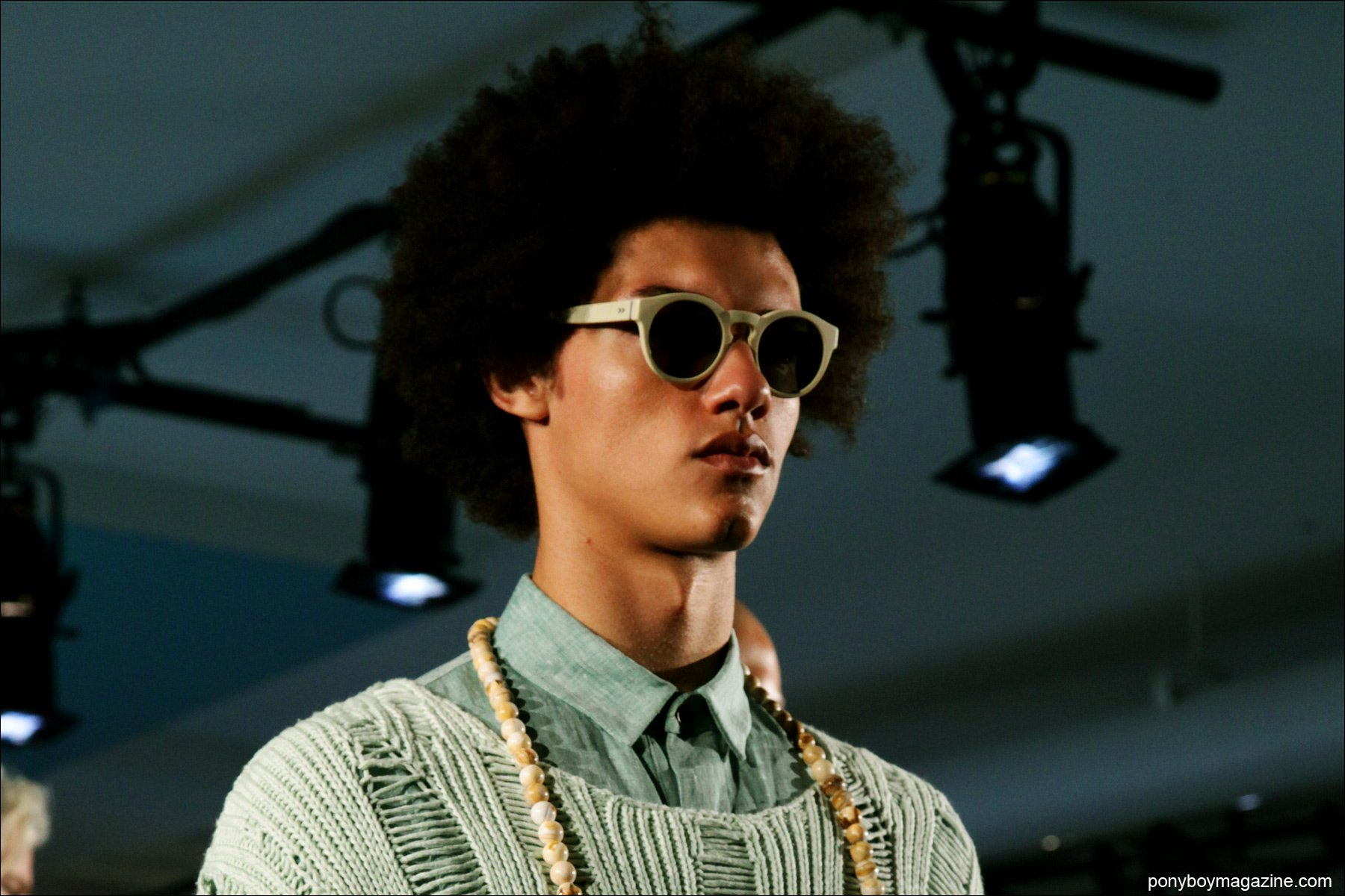 A male model in an afro and sunglasses at Rochambeau S/S 2015 presentation at Milk Made. Photograph by Alexander Thompson.