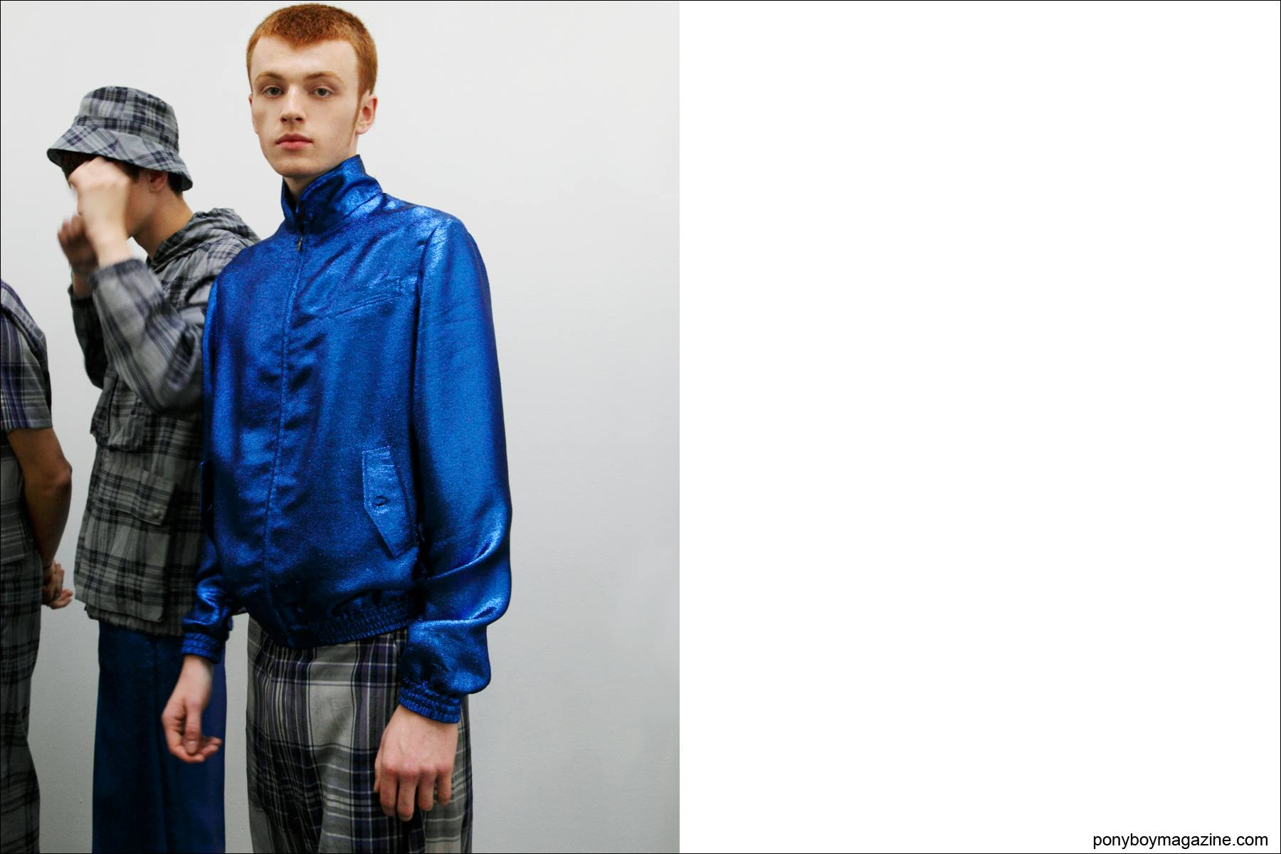 A male model photographed backstage in a metallic blue jacket designed by Duckie Brown, S/S 2015. Photograph taken at Industria Studios in New York City by Alexander Thompson for Ponyboy Magazine.