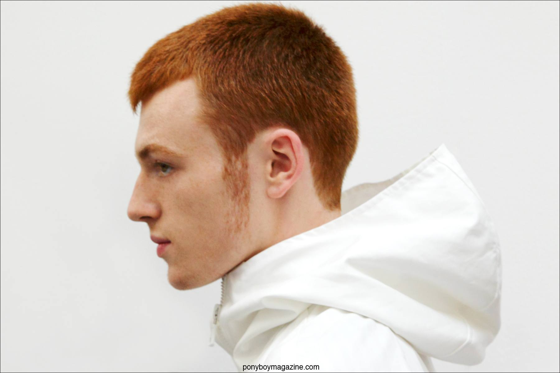 A red-headed male model wears a hooded jacket designed by Duckie Brown S/S15. Photographed at Industria Studios in New York by Alexander Thompson for Ponyboy Magazine.