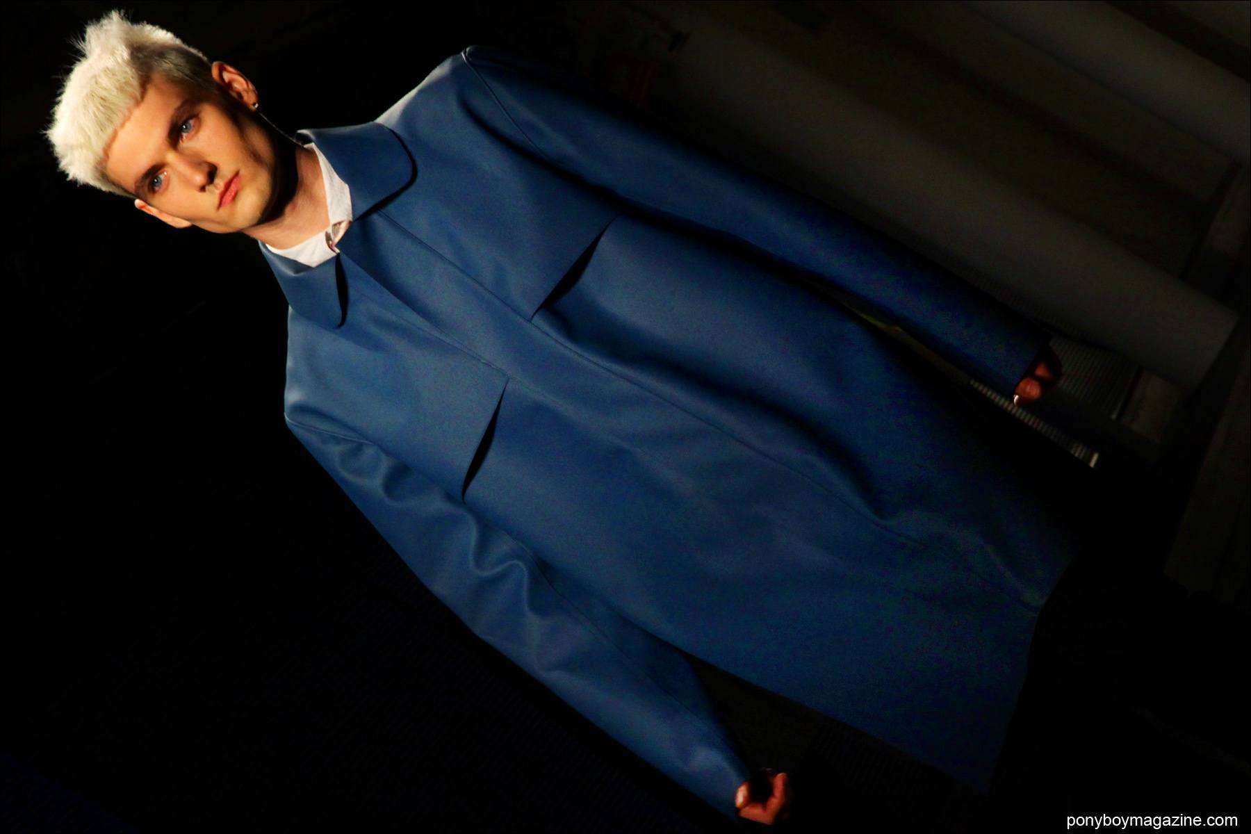 Male model James Magnum III walks in a vivid blue men's trench coat for Patrik Ervell S/S15 collection at Milk Studios. Photograph by Alexander Thompson for Ponyboy Magazine.