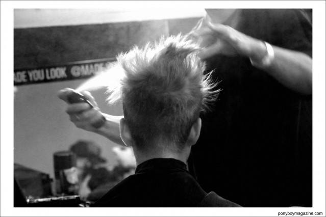 A male model gets his hair sprayed, backstage at Patrik Ervell S/S15. Photograph by Alexander Thompson for Ponyboy Magazine.