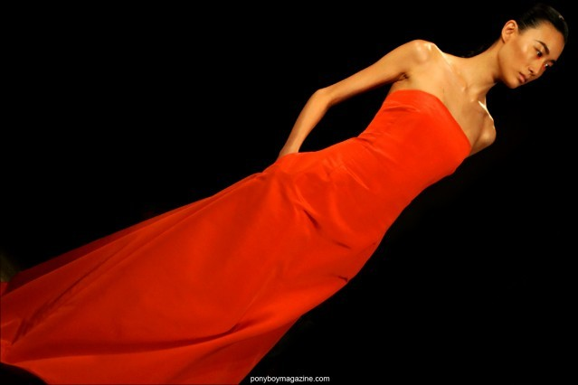 A strapless red gown on the runway, designed by Peter Som, Spring/Summer 2015. Photographed by Alexander Thompson for Ponyboy Magazine.