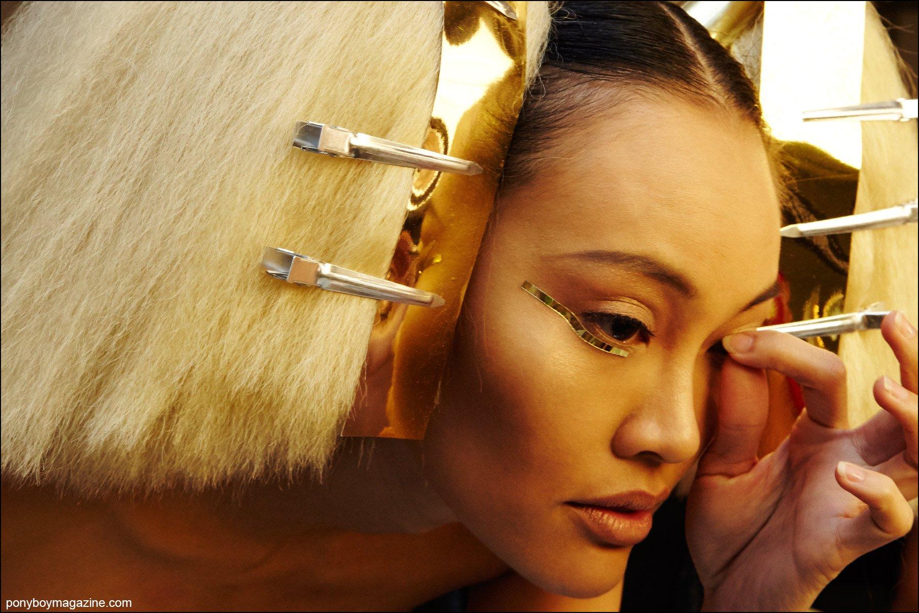A model backstage adjusts her false eyelash, photographed at the Blonds S/S16 show by Alexander Thompson for Ponyboy magazine NY.