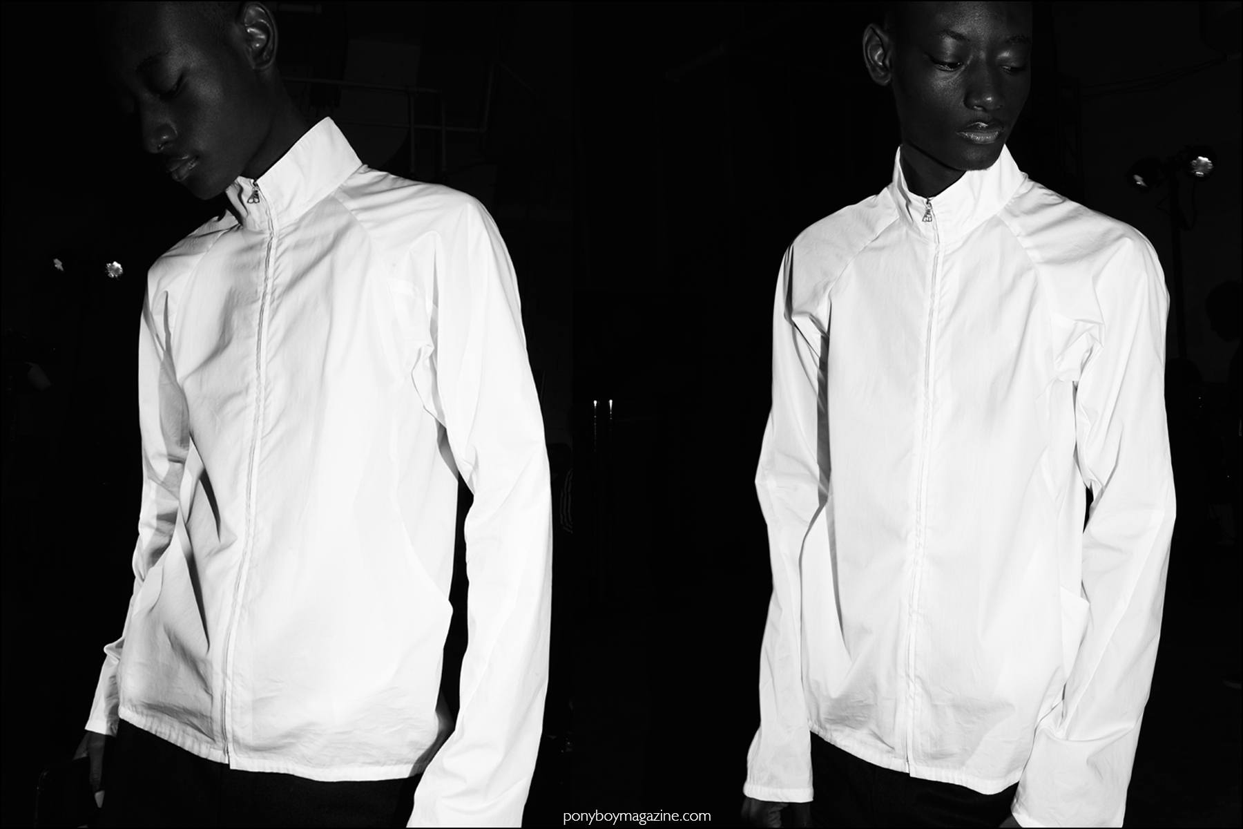 Male model Youssouf Bamba in a white jacket, photographed backstage at Duckie Brown F/W16 menswear show. Photography by Alexander Thompson for Ponyboy magazine NY.