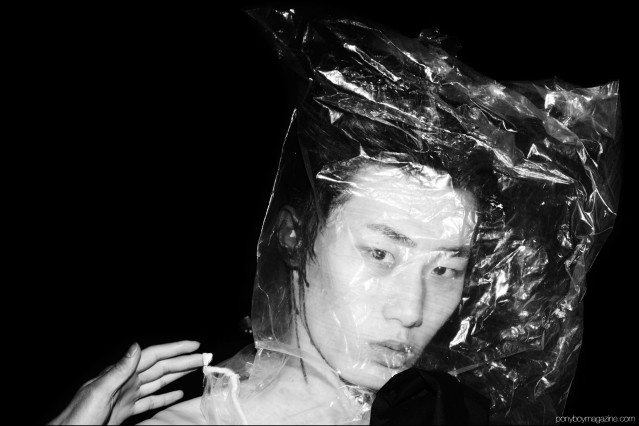 A male model photographed backstage with a plastic bag over his head, at the Siki Im + Den Im F/W16 menswear show. Photography by Alexander Thompson for Ponyboy magazine.