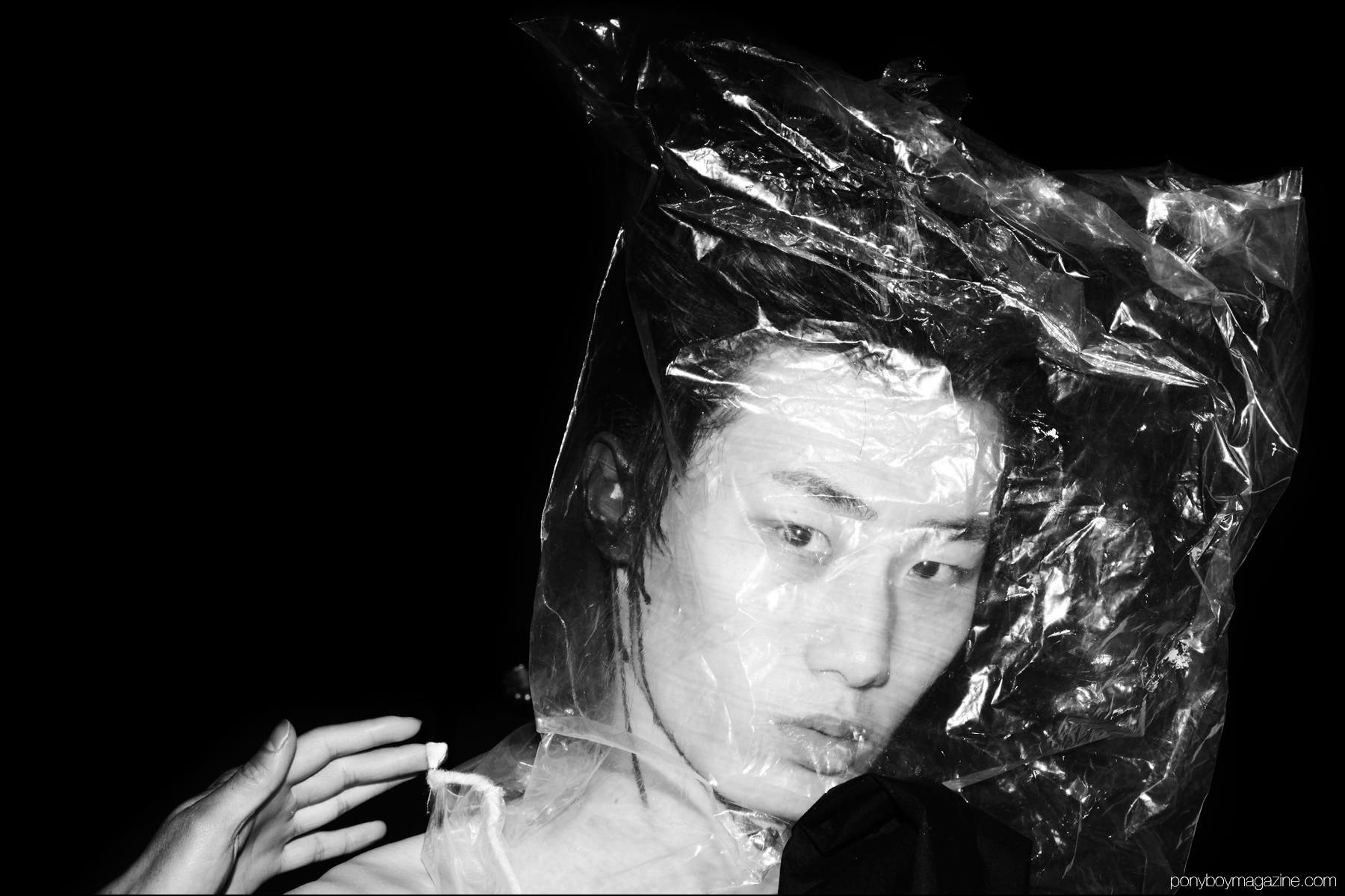 A male model photographed backstage with a plastic bag over his head, at the Siki Im + Den Im F/W16 menswear show. Photography by Alexander Thompson for Ponyboy magazine NY.