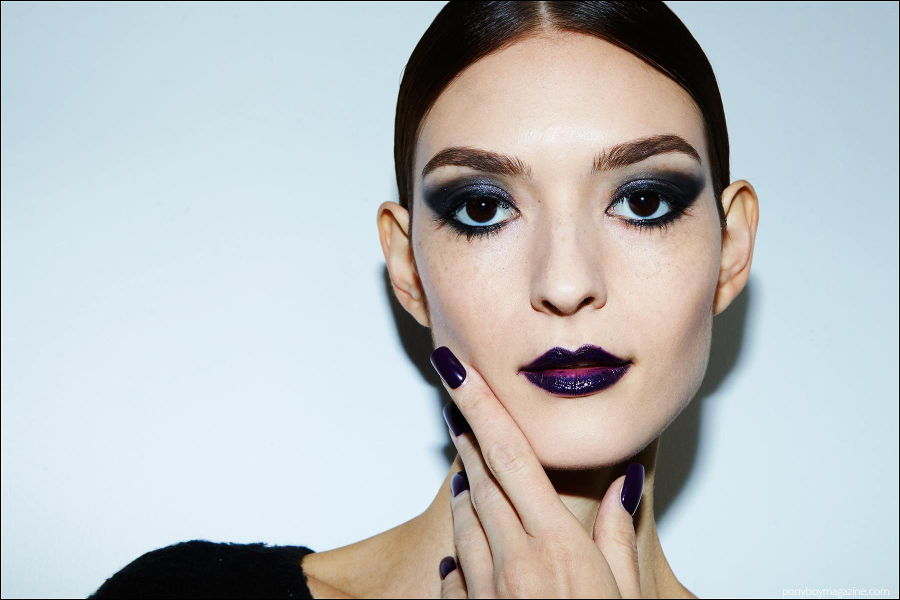 Beauty shot of a model with purple eyeshadow, lips and nails. Photographed backstage at Georgine F/W16 womenswear show by Alexander Thompson for Ponyboy magazine NY.