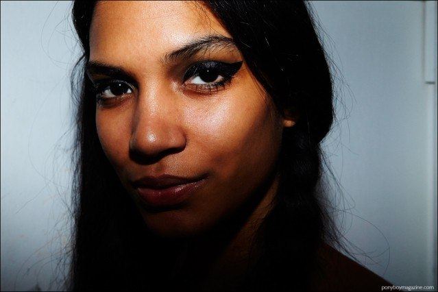 Close-up photo of a model's dramatic black cat eye makeup, backstage at Libertine F/W16. Photography by Alexander Thompson for Ponyboy magazine.