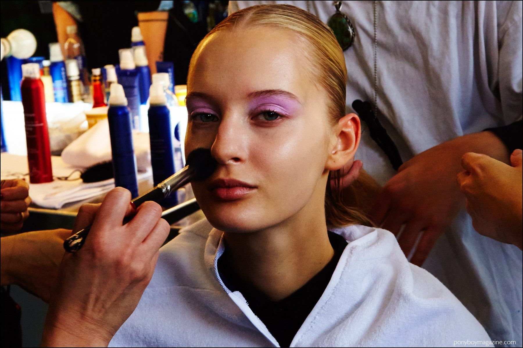 A blonde model photographed backstage in makeup, for Milly F/W16. Photography by Alexander Thompson for Ponyboy magazine NY.