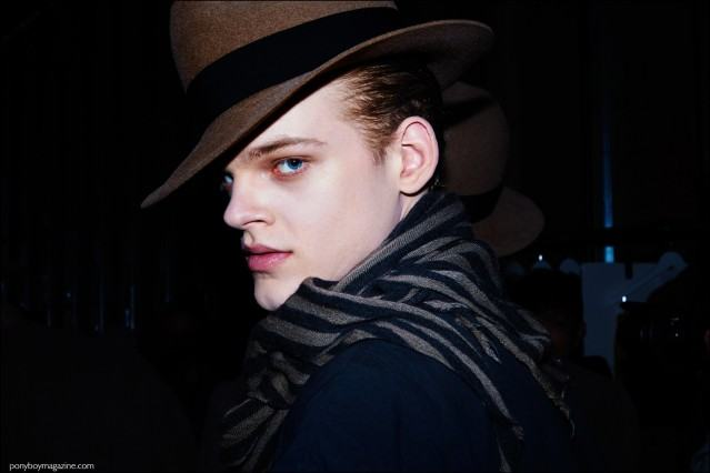 Model Reid Rolling photographed in a fedora, backstage at Robert Geller F/W16 menswear show. Photography by Alexander Thompson for Ponyboy magazine.