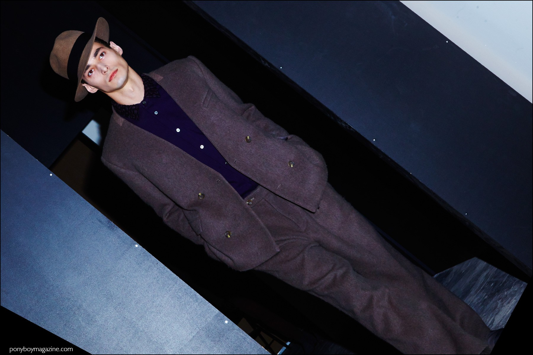 A suit and fedora worn backstage by a male model, for Robert Geller F/W16 menswear show. Photography by Alexander Thompson for Ponyboy magazine NY.
