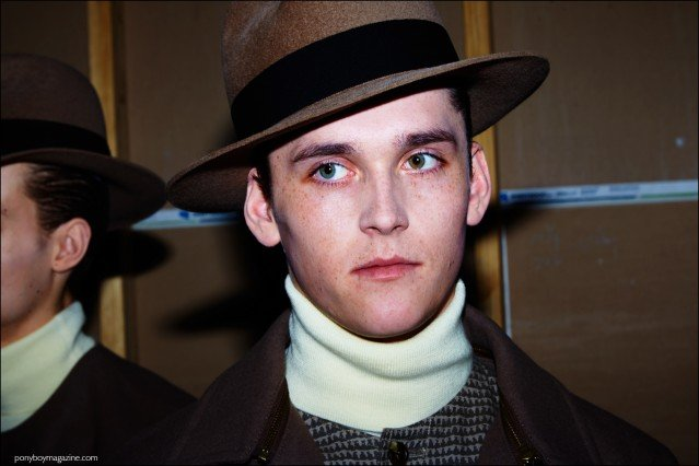 Model Anders Hayward wears a fedora, backstage at Robert Geller F/W16 menswear show. Photography by Alexander Thompson for Ponyboy magazine.