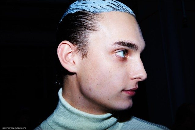 Male model Kyle Mobus, photographed backstage with slicked back hair at Robert Geller Fall/Winter 2016 menswear show. Photography by Alexander Thompson for Ponyboy magazine.