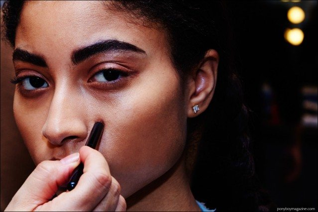 A model snapped backstage in makeup, at A Détacher Fall 2016 womenswear show. Photography by Alexander Thompson for Ponyboy magazine.