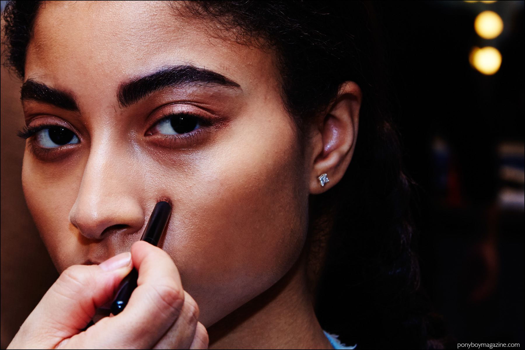 A model snapped backstage in makeup, at A Détacher Fall 2016 womenswear show. Photography by Alexander Thompson for Ponyboy magazine NY.