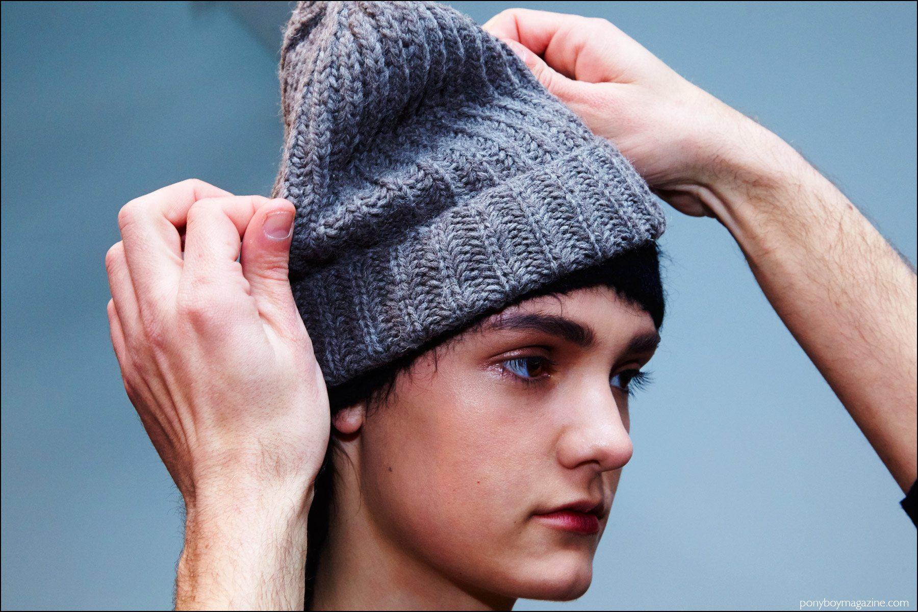 A model gets her wool cap adjusted backstage at A Détacher Fall 2016 womenswear show. Photography by Alexander Thompson for Ponyboy magazine NY.