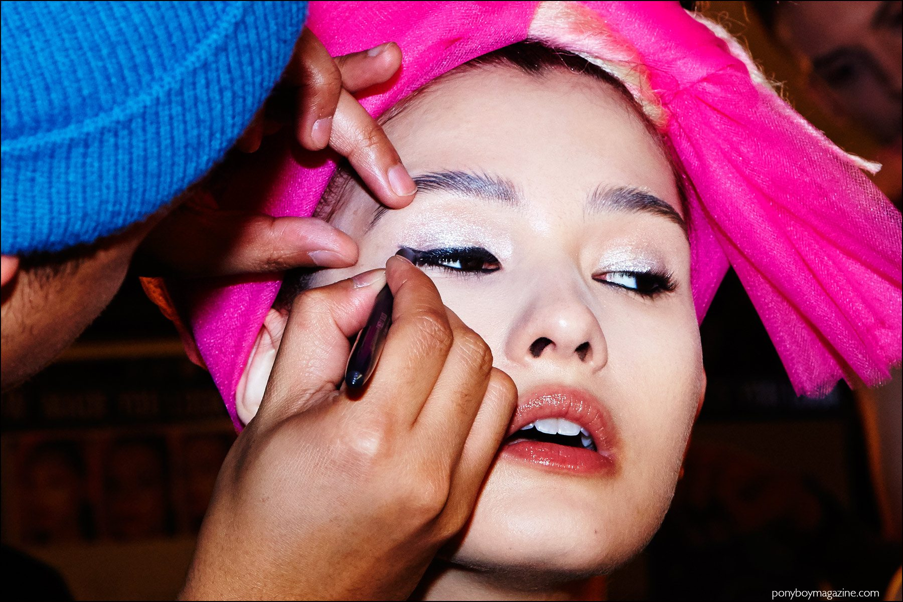 A model gets her eye makeup applied by a MAC cosmetics artist, backstage at The Blonds F/W16 womenswear show. Photography by Alexander Thompson for Ponyboy magazine NY.