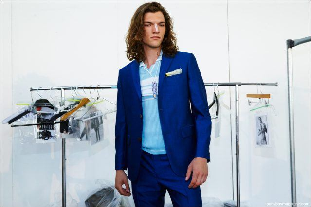 A male model in a blue David Hart S/S17 suit, photographed backstage by Alexander Thompson for Ponyboy magazine.