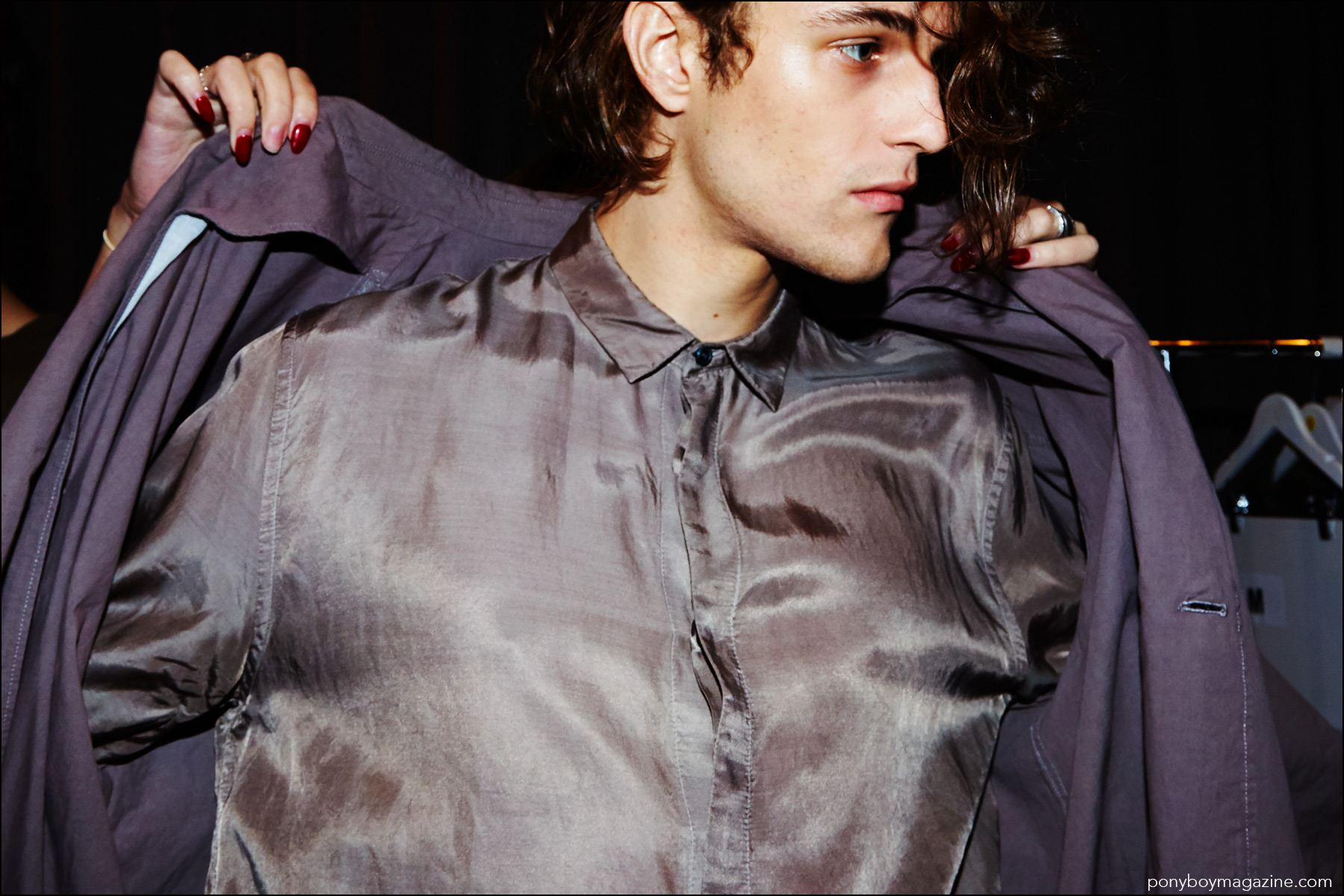 A close-up shot of a male model getting dressed backstage at the Robert Geller Spring/Summer 2017 menswear show. Photography by Alexander Thompson for Ponyboy magazine NY.