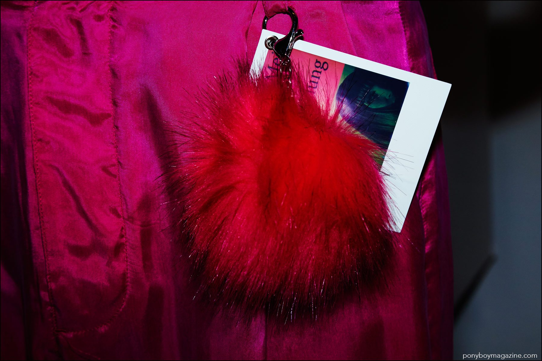 A detail shot of a fur pom-pom keychains and polaroid on men's trousers, photographed backstage at the Robert Geller Spring/Summer 2017 menswear show. Photography by Alexander Thompson for Ponyboy magazine NY.