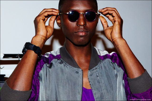 A male model adjusts his sunglasses, backstage at Robert Geller Spring/Summer 2017 menswear show. Photography by Alexander Thompson for Ponyboy magazine.