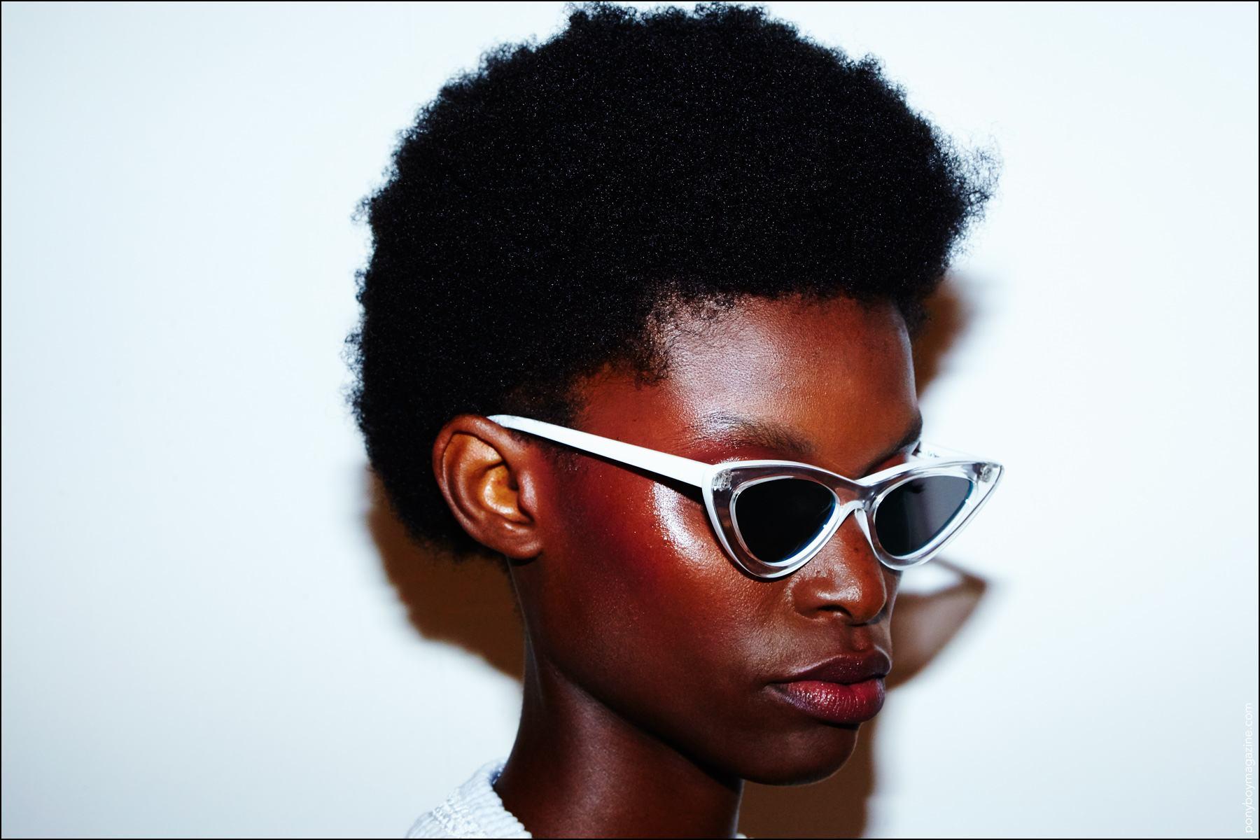 A model in afro and cat-eye glasses snapped backstage before walking for Adam Selman S/S17 show. Photography by Alexander Thompson for Ponyboy magazine.