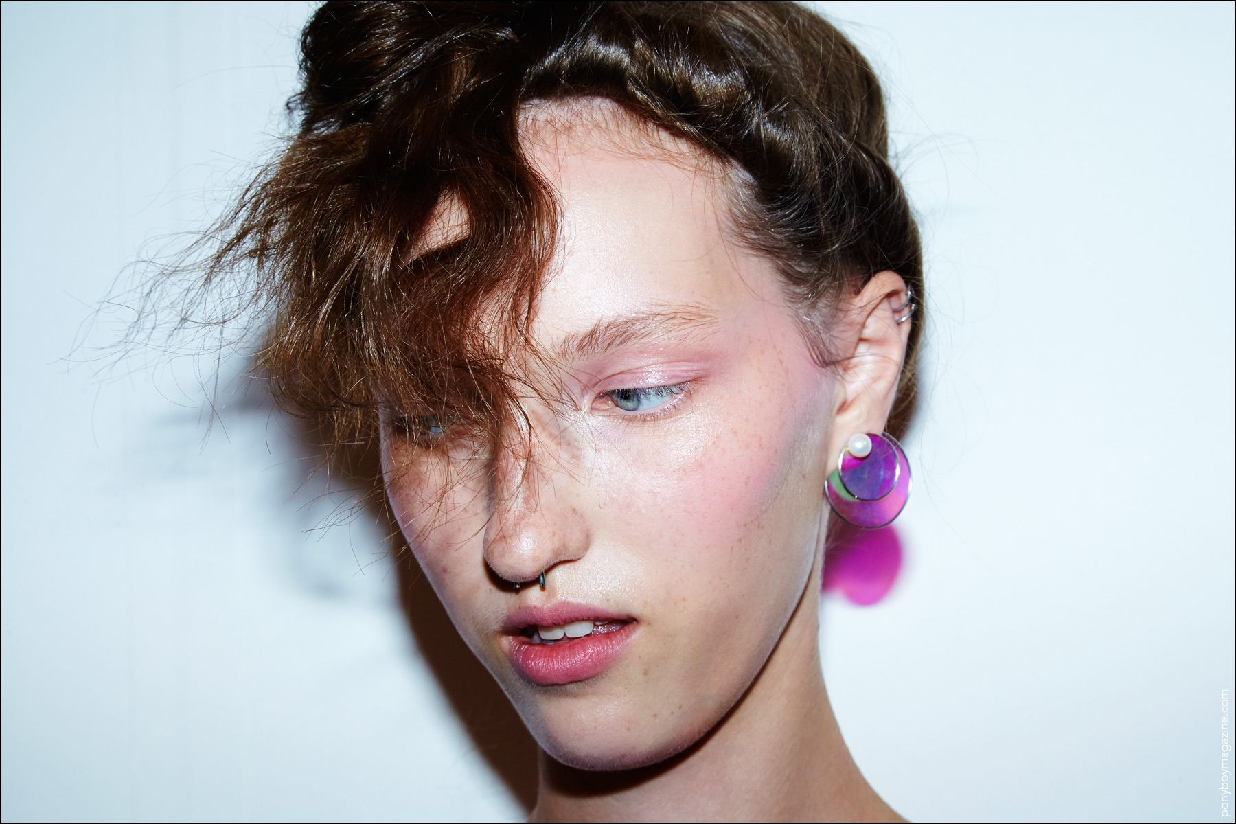 A close-up shot of a plastic disc earring designed by Adam Selman for S/S17. Photography by Alexander Thompson for Ponyboy magazine.