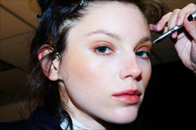 A brunette model gets her makeup applied backstage at the Adam Selman Fall 2017 womenswear show. Photographed by Alexander Thompson for Ponyboy magazine.