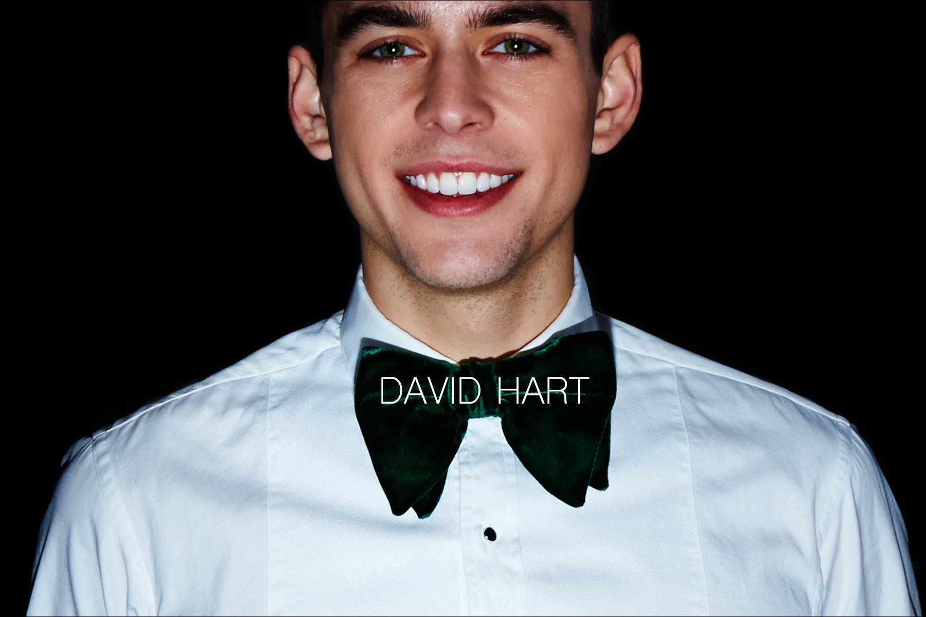 A smiling male model snapped backstage wearing a David Hart bowtie and tuxedo shirt for Fall/Winter 2017. Photography by Alexander Thompson for Ponyboy magazine.