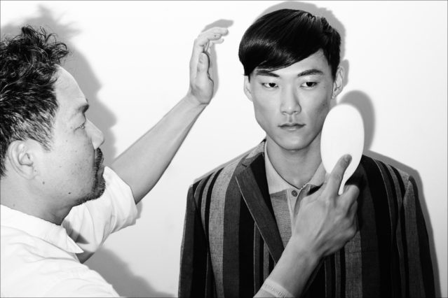 Kien Hoang for Oribe puts finishing touches on a male model, backstage at the David Hart Spring 2018 menswear show. Photography by Alexander Thompson for Ponyboy magazine.