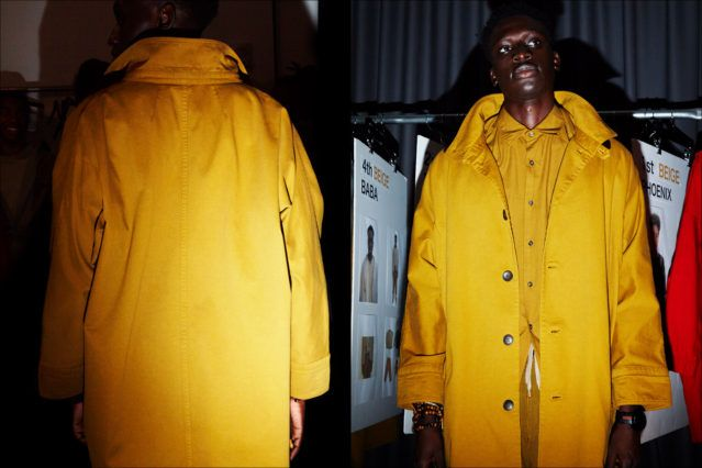 A mustard trench coat snapped backstage at Gustav Von Ashcenbach Spring 2018 menswear show by designer Robert Geller. Photographed by Alexander Thompson for Ponyboy magazine.