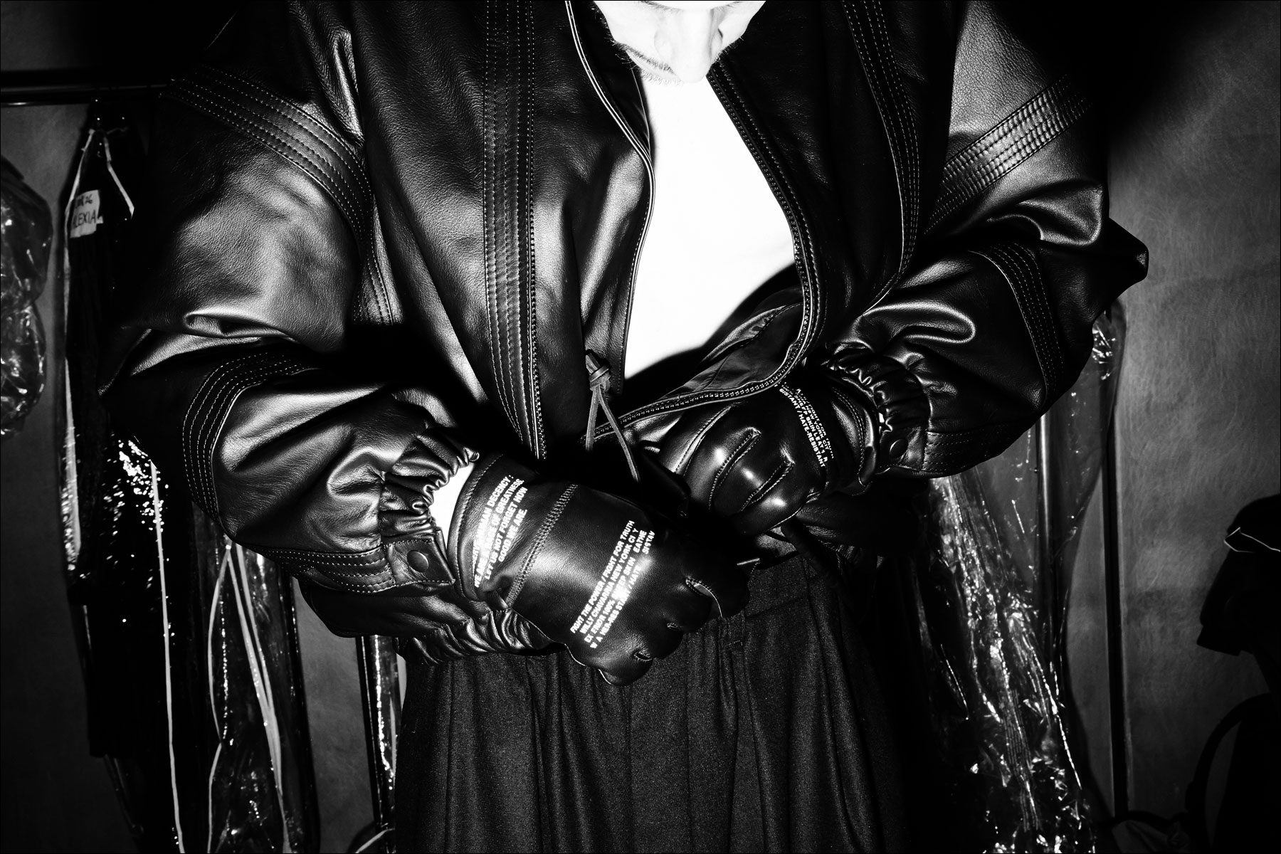 A model adjusts his leather jacket backstage at the Willy Chavarria menswear show for Fall 2018. Photography by Alexander Thompson for Ponyboy magazine.