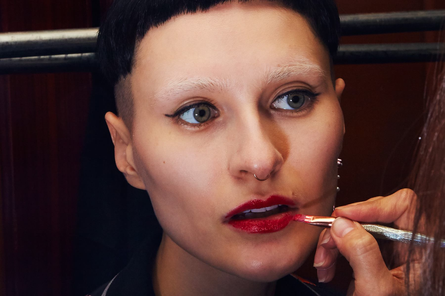 Close-up shot of a model getting makeup application at Snow Xue Gao Fall/Winter 2018. Photographed by Alexander Thompson for Ponyboy magazine.