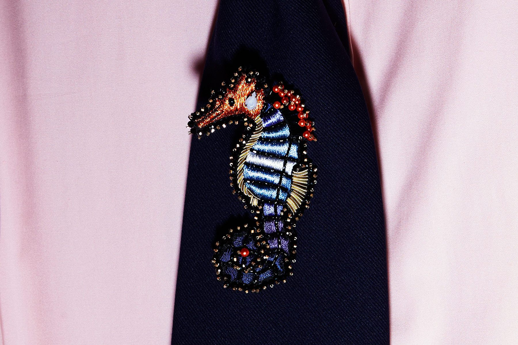 Close-up of a seahorse embroidery on a tie photographed backstage at David Hart for Spring/Summer 2019.