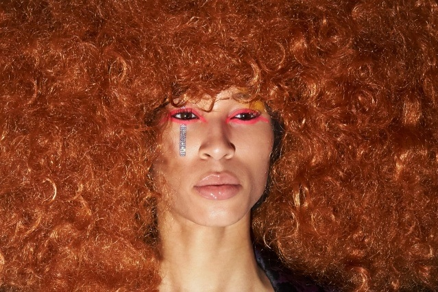 A model's very colorful makeup & exaggerated wig photographed backstage at the Laurence & Chico F/W 2019 collection. Photographed by Alexander Thompson for Ponyboy magazine.