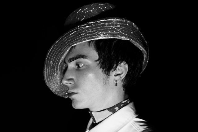 A male model backstage in a hat for Dirty Pineapple by J.R Malpere/Commando. Photography by Alexander Thompson for Ponyboy magazine.